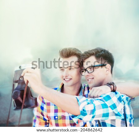 two boys doing selfy by retro camera - stock photo