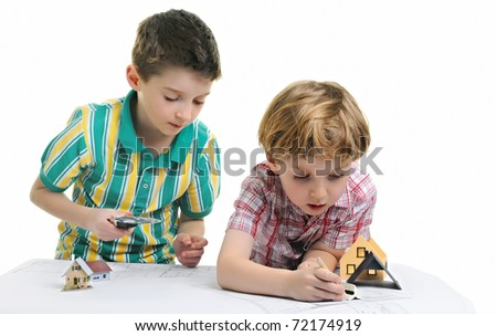 two boys drawing and playing with house models on architect's plans - stock photo