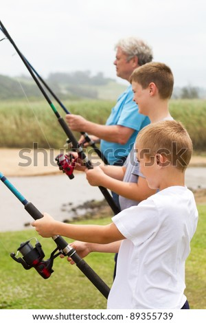 two boys fishing with their grandpa by the river - stock photo