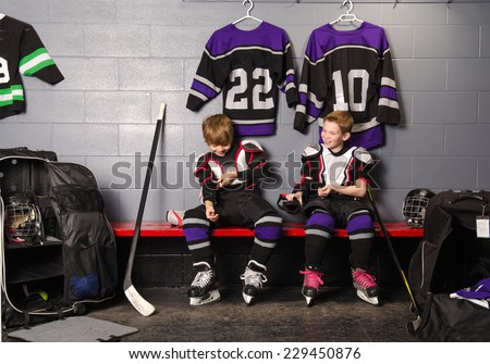 Two Boys Get Dressed in hockey gear in dressing room before game - stock photo