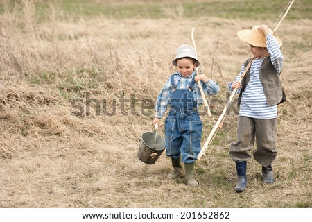 Two boys go fishing in the river with fishing equipment and tackle - stock photo