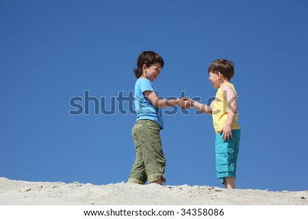 Two boys greet on sand - stock photo