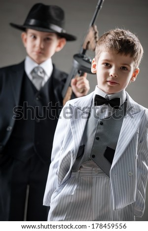Two boys in a gangsters with a gun on a black background - stock photo