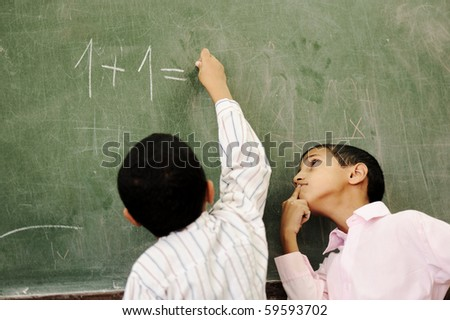 Two boys in classroom thinking, writing and counting on board - stock photo