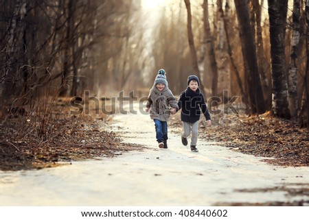 Two boys in coats, hats and jeans running along a path in the forest and holding hands  - stock photo