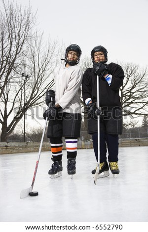 Two boys in ice hockey uniforms holding hockey sticks standing on ice rink in ice skates. - stock photo