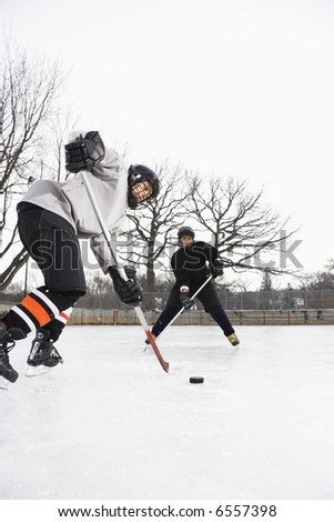 Two boys in ice hockey uniforms skating on ice rink moving puck. - stock photo