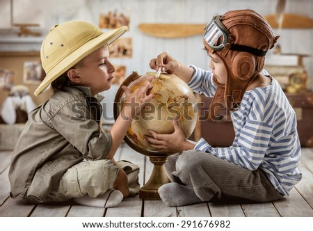 Two boys in the form of pilot and tourists planning on a globe of their travel route - stock photo