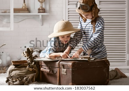 Two boys in the form of pilot and traveler read the old card in my room - stock photo
