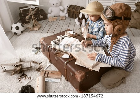 Two boys in the images of the pilot and the traveler fill your travel book - stock photo