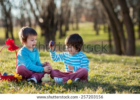 Two boys in the park, having fun with colored eggs for Easter, springtime