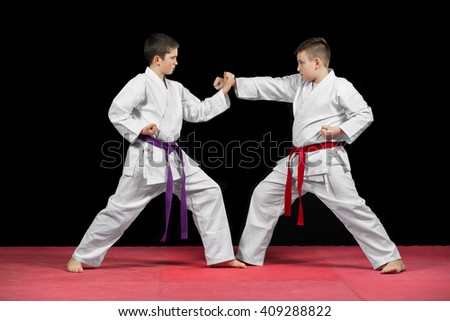 Two boys in white kimono fighting isolated on black background. - stock photo