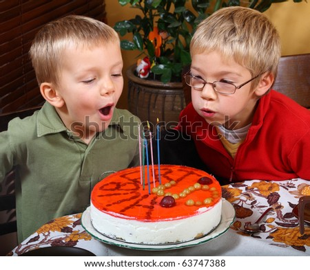Two boys is blowing candles on birthday cake - stock photo