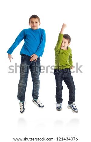 Two boys jumping on white background. Studio shot. - stock photo