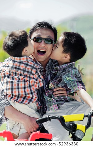 Two boys kissing their father's cheeks while he holds them in his arms - stock photo