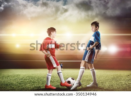 Two boys of school age playing football on stadium - stock photo