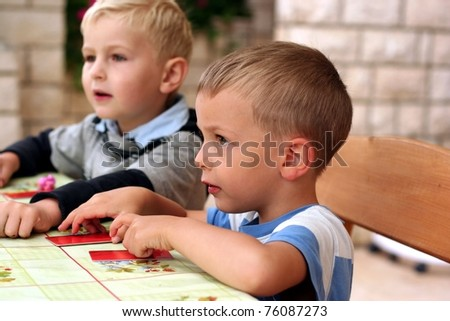 Two boys play a board game, looking forward to somebody - stock photo