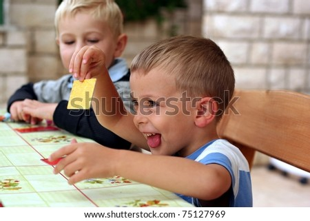 Two boys play a board game, one boy shows a card - stock photo