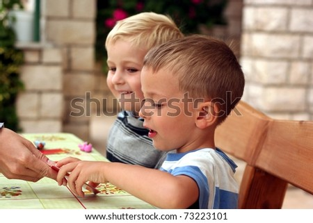 Two boys play a board game, one boy takes a card from a hand - stock photo