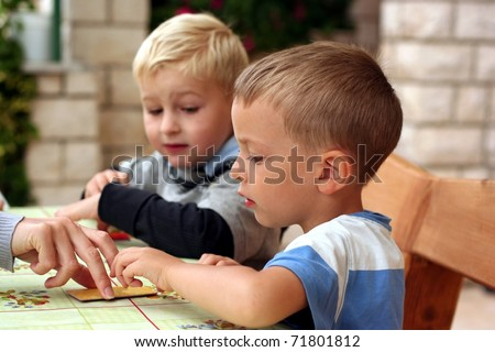 Two boys play board game, they look to hand with a card - stock photo