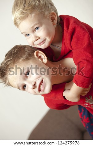 Two boys playing and embracing at home - stock photo