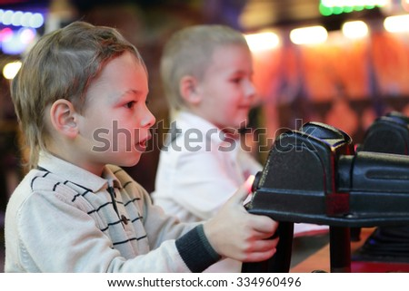 Two boys playing at the indoor amusement park - stock photo