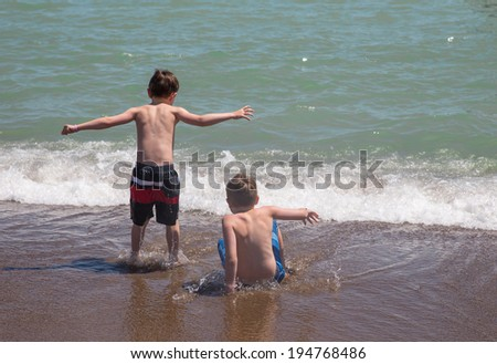 Two boys playing on the beach of a sea