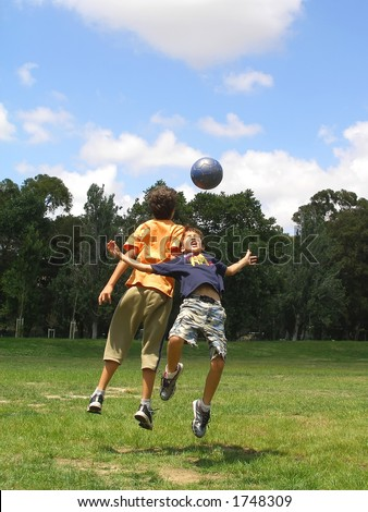 Two boys playing soccer in a green grass field with blue sky above - stock photo