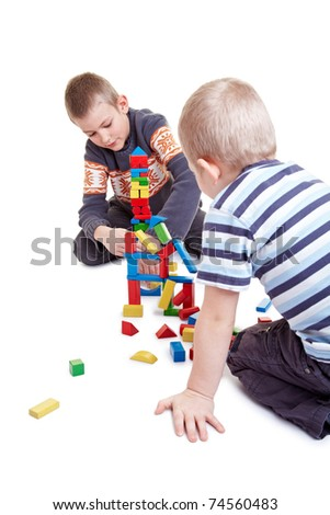 Two boys playing together with many building bricks - stock photo