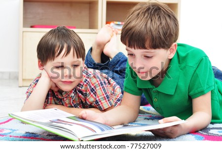 Two boys reading a book together