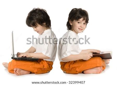 Two boys (reflecnbon) - one wish laptop, other reading - stock photo