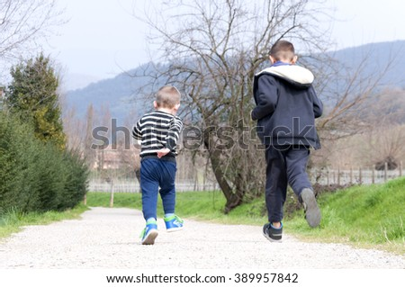 two boys run on rural road