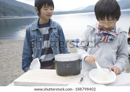 Two boys serving boiled rice by lakeside