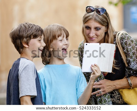 Two Boys Showing Something to Mother on Tablet