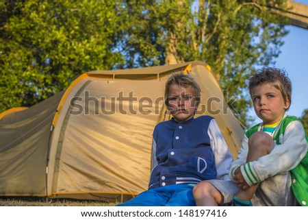 two boys sitting in front of a tent, looking at the sunset - stock photo