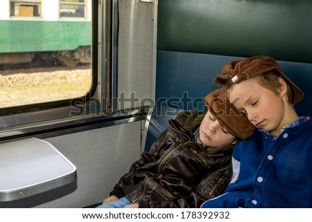 two boys sleeping in a train during their travel - stock photo