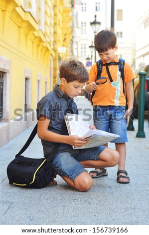 Two boys studying a map on the city street - stock photo