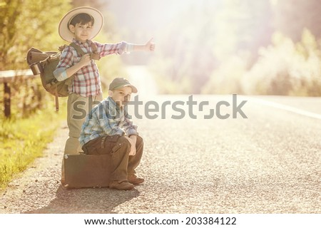 Two boys travel on mountain roads with backpacks hitchhiking - stock photo