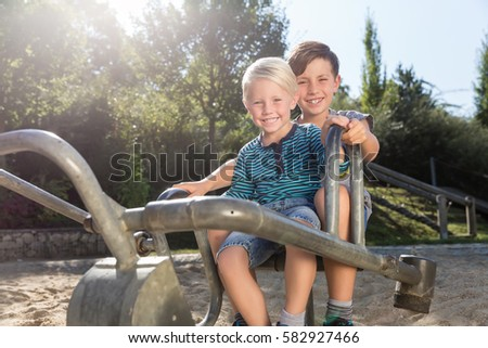 Two boys using digger on adventure playground in park