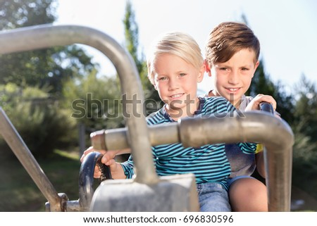 Two boys using digger on adventure playground in park having fun