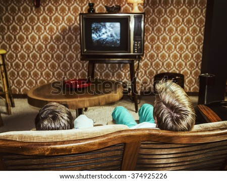 two boys watching television at home in 50's style, shot from behind - stock photo