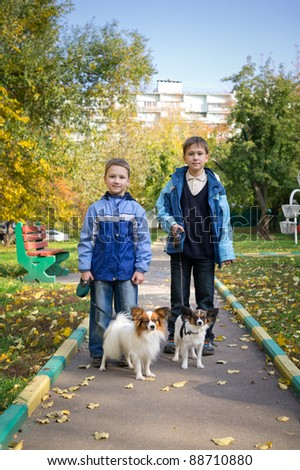 Two boys with dogs in autumn park - stock photo