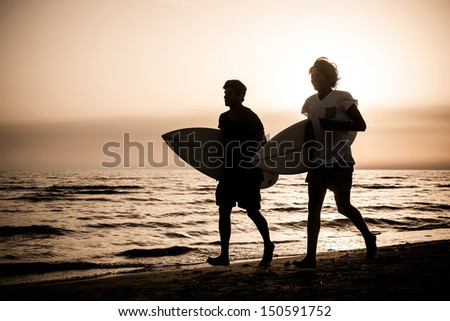 Two Boys with Surf Boards at Sunset - stock photo