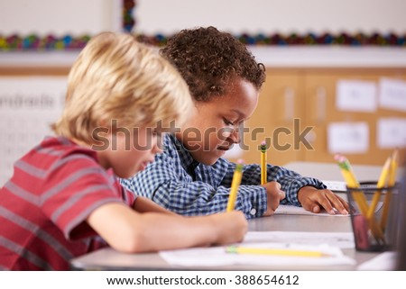 Two boys working at their desks in elementary school class - stock photo