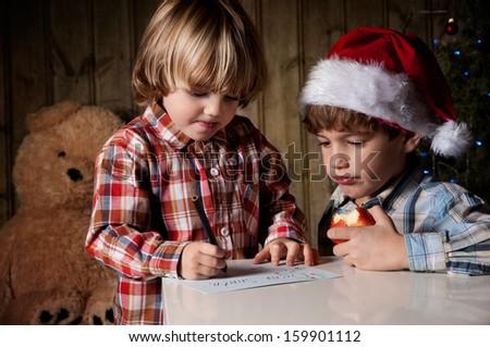 Two boys write a letter to Santa - stock photo