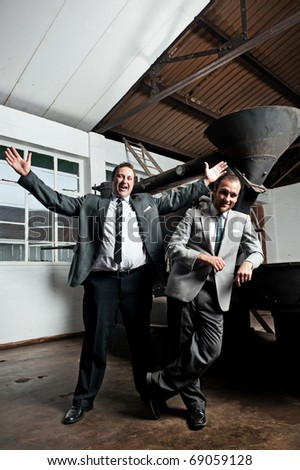 two brave businessmen stand excited next to their factory machine - stock photo