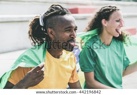 Two brazilian sport fans celebrating their country - Multiracial supporters having fun at stadium for olympic games - Vintage desaturated retro filter - stock photo