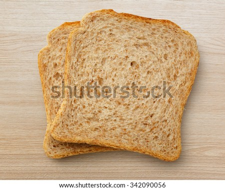 Two bread slices on the wooden background