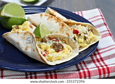 Two breakfast tacos with sausage, cheese, and peppers.  Garnished with fresh lime.
