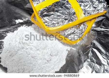 Two bricks of cocaine wrapped in foil beside a heap of cocaine. - stock photo